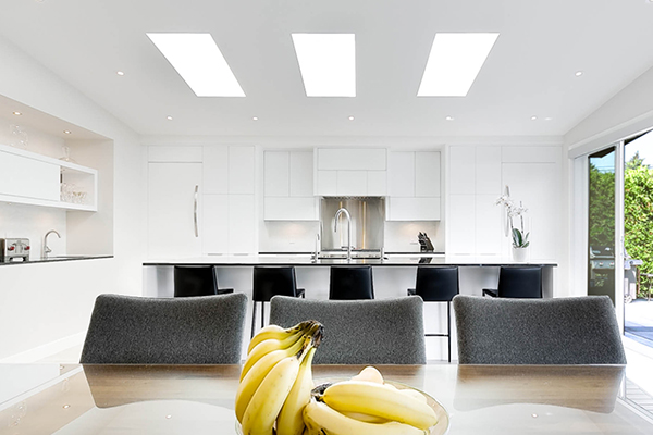 agrandissement intérieur cuisine moderne îlot central puit de lumière portes patios aire ouverte armoires blanches  enlargement interior kitchen island modern skylight bay window open area white cabinet