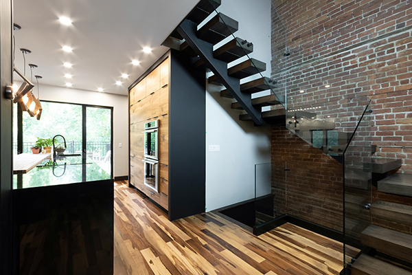 rénovation cuisine ouverte escalier noir limon central mur brique garde-corps verre électroménager luxe Thermador renovation open kitchen staircase black central stringer wall brick glass guardrails standoff oven Thermador