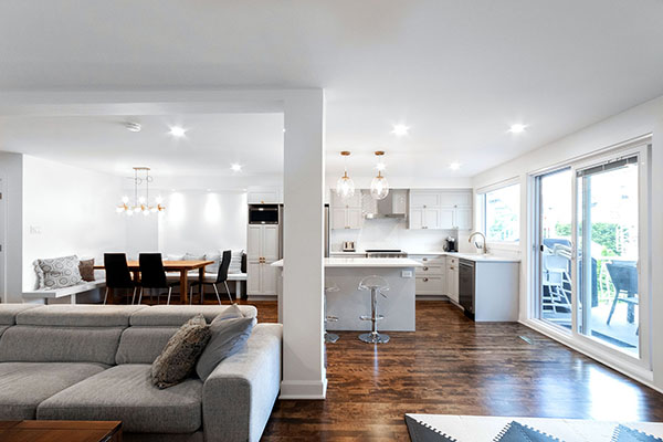 rénovation intérieur ouverture mur porteur aire ouverte luminosité cuisine blanche avec îlot salon ouvert porte patio renovation interior supporting wall opening open area bright kitchen island white opened living-room bay window